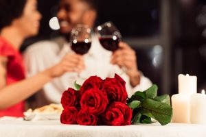 Couple toasting with red wine. Bouquet of roses and candles in foreground.