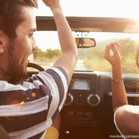 Couple in a car on an empty road, one of the benefits of midweek travel