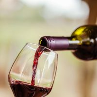 Red wine being poured in a glass. Visit Bennett Vineyards for a taste of delicious wine.