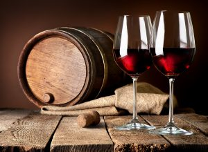 Barrel and wineglasses of red wine on a wooden table. Visit Ancien Winery