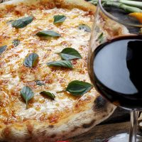 Whole pizza with a glass of wine
