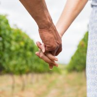Couple holding hands in a vineyard on a romantic getaway to Napa Valley