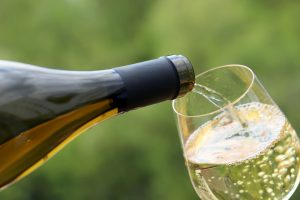 White wine pouring from the bottle into the glass on green nature blurred background