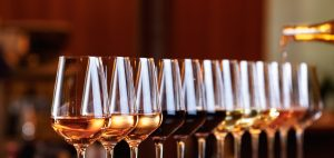 Wine glasses in a row. Pouring wine. Buffet table celebration of wine tasting. Nightlife, celebration and entertainment concept. Horizontal, wide screen banner format (Wine glasses in a row. Pouring wine. Buffet table celebration of wine tasting. Nigh