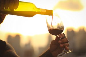 Person pouring red wine at sunset. Red wines like this can be enjoyed at Whetstone Wine Cellars