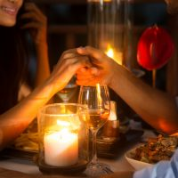 Couple holding hands over candlelight at dinner at one of the romantic restaurants in Napa CA